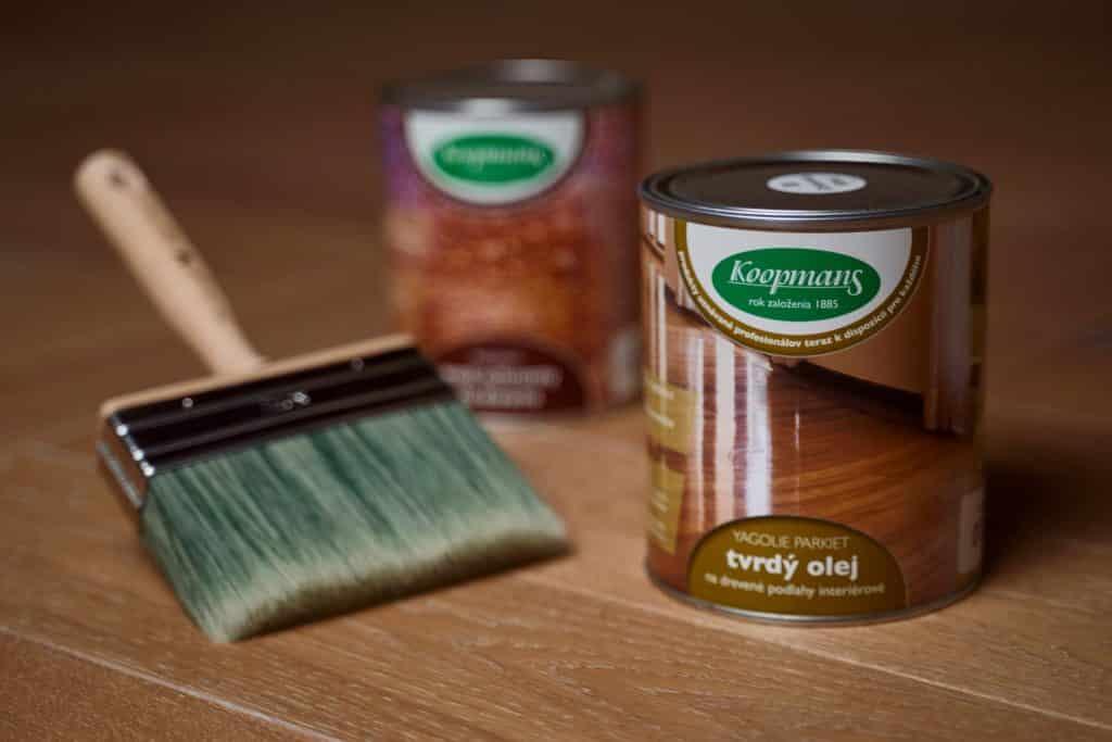 Na dreveneých parketách je položená pixla farby YAGOLIE, pixla farby YAGWAX a maliarska štetka.