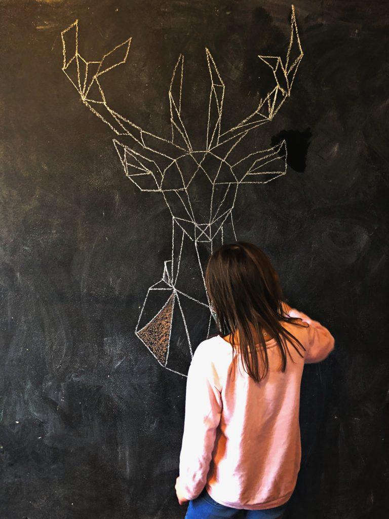 Dievča kreslí na čieru tabuľovú stenu geometrického jeleňa kriedou.