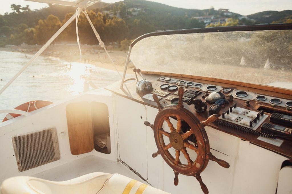 Západ slnka po nad loďku, ktorá je na mori. Detailný záber na kormidlo.