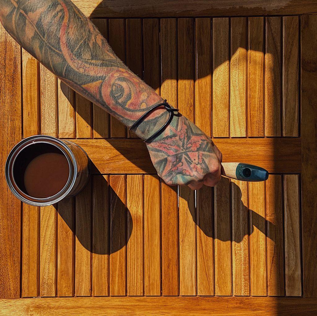 Pohľad zhora na terasový stôl, na ktorom je položená otvorená pixla s farbou a chlapská ruka štetcom prechádza po povrchu.