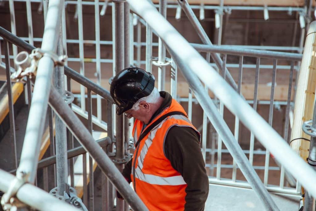 Robotník v prilbe pracujúci na kovovej konštrukcii.
