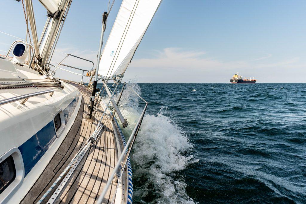 Jachta, ktorá sa plaví šírim morom. Detailný záber na bočnú stranu jachty.