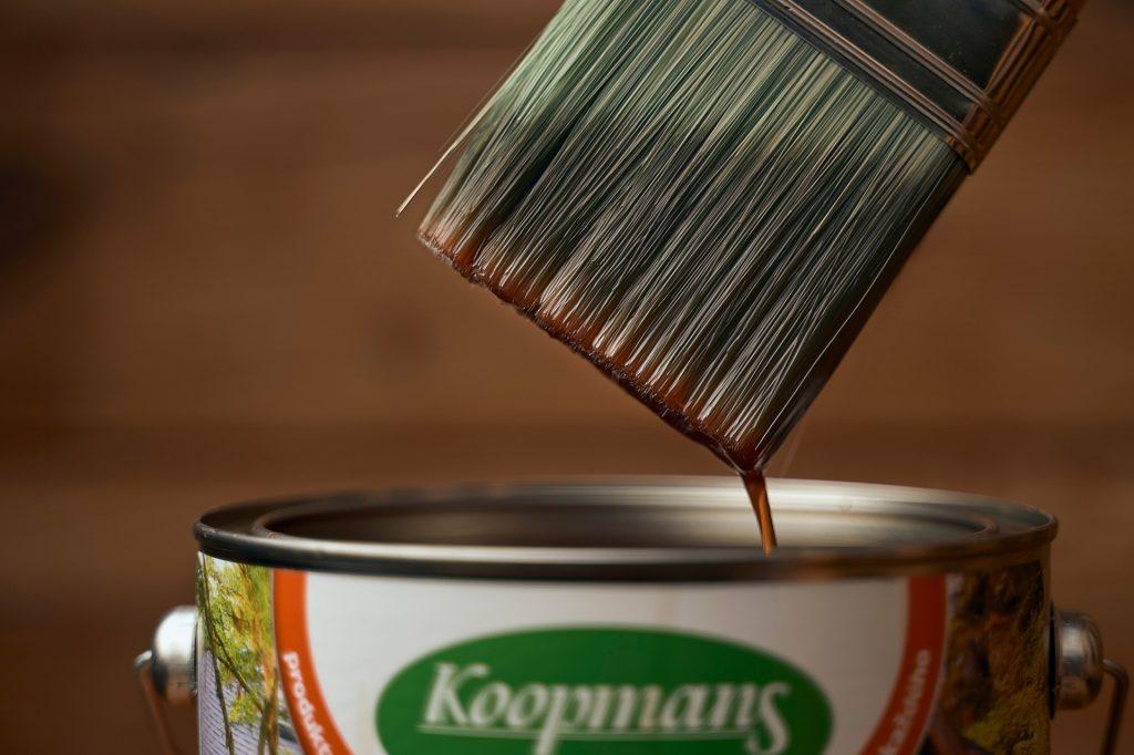 Detailný záber na štetec, ktorý je práve vytiahnutý z plechovsky s olejovou farbou. Farba steká zo štetca naspäť do plechovky.