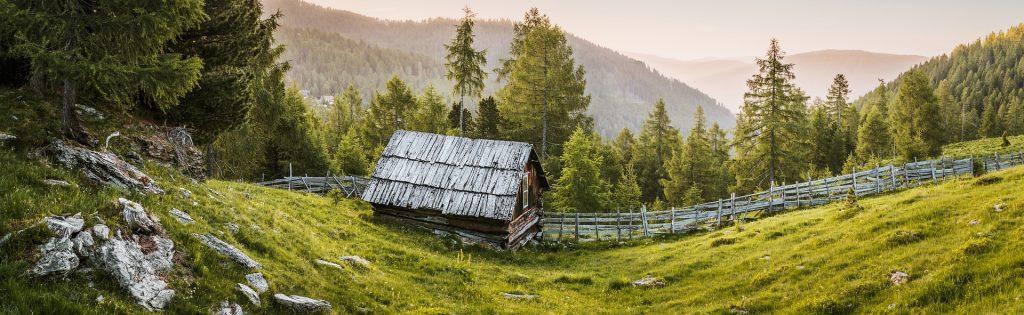 Panoramatická fotografia, na ktorej je drevená chatka v prírode s výhľadom na panorámu z kopcov.