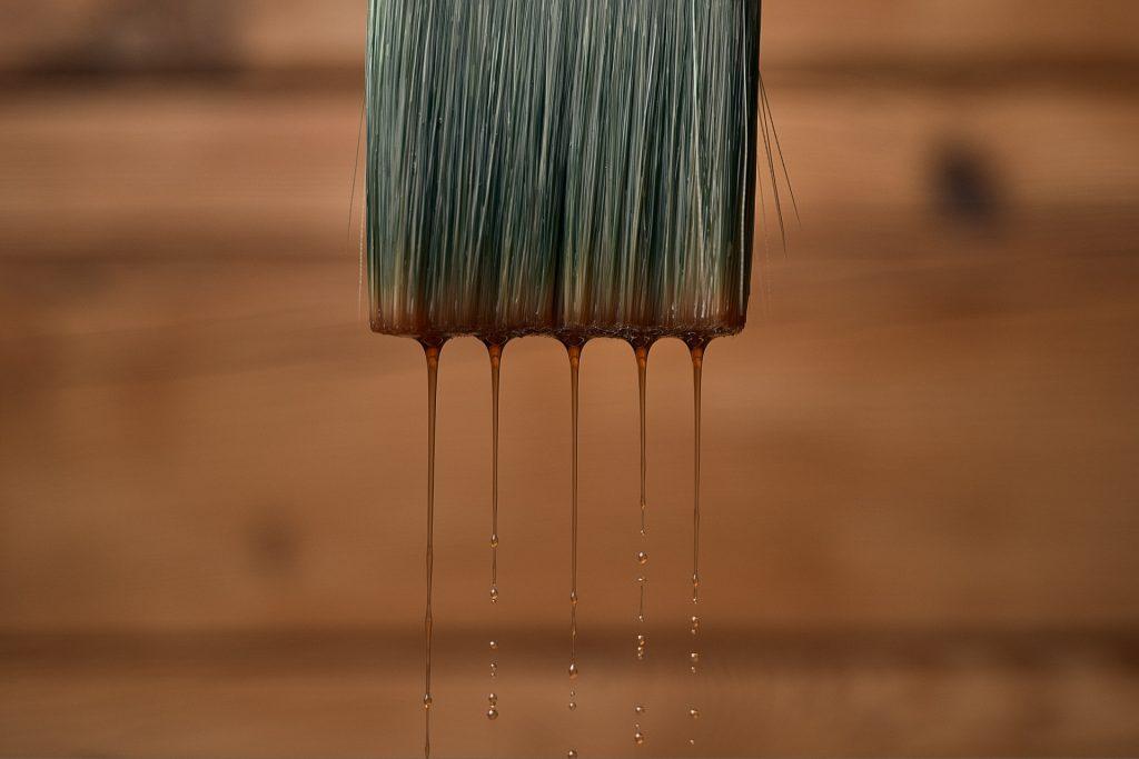 Detailný záber na plochý štetec, z ktorého steká olejová farba.