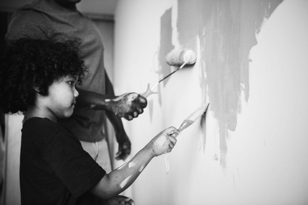 Čierno biela fotografia, na ktorej dieťa s otcom maľuje stenu v interiéri.