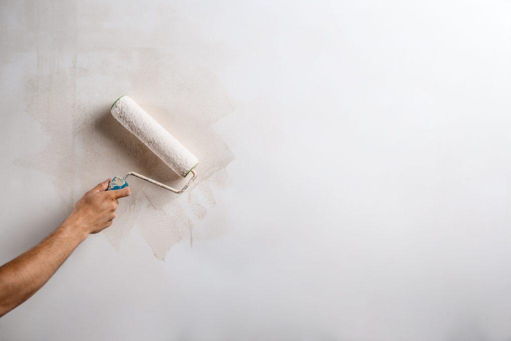 Detailný záber na ruku, ktorá drží valček a maľuje stenu na bielo.